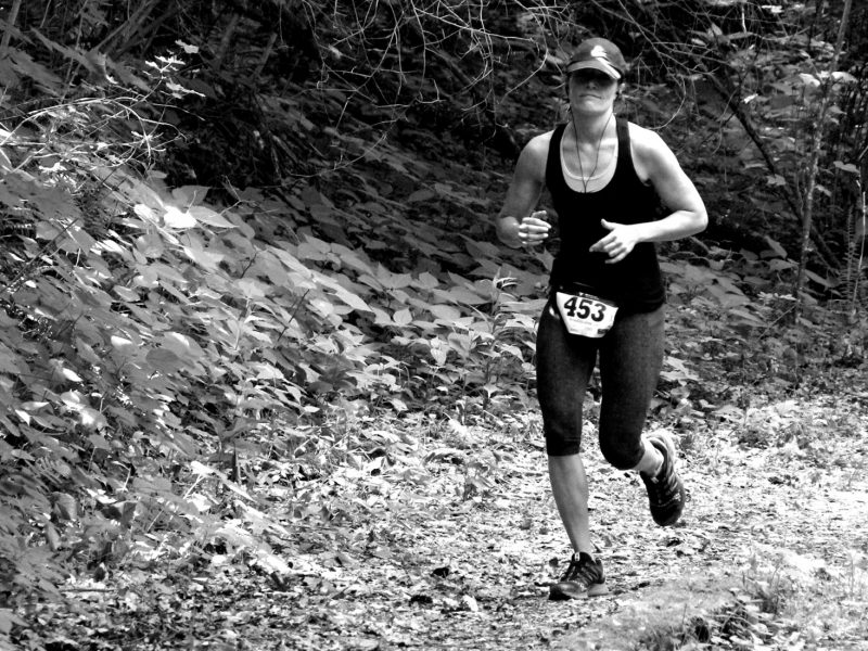 A woman running through the forest while competing in a wilderness adventure race on a trail in the new river gorge in west virginia