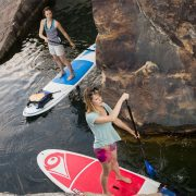 girls stand up paddleboarding between the rocks