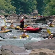 guides instruct kayakers down a summer gauley adventure