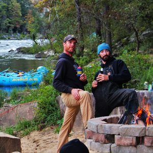 a couple of guys hang out by the campfire on an overnight gauley trip