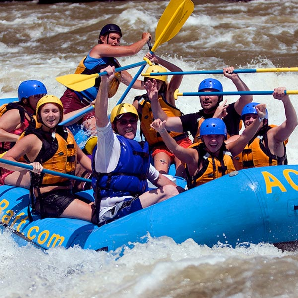 A group of rafters cheer as they defeat a large rapid