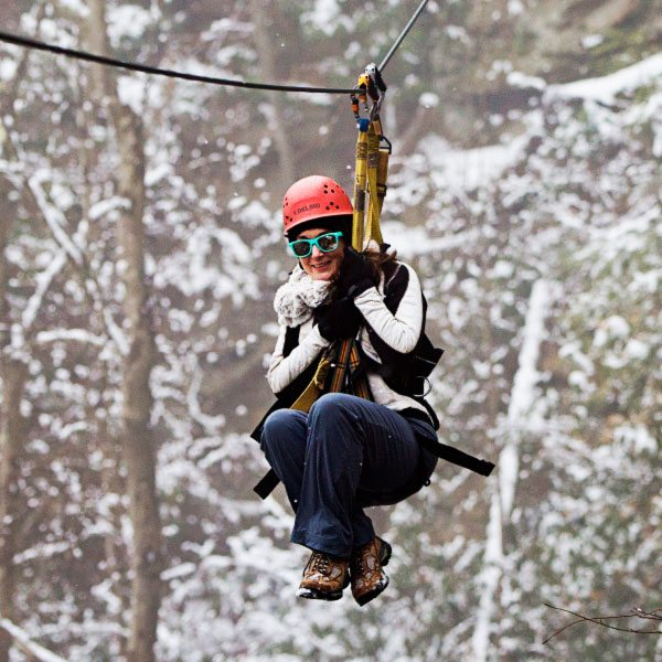 A girl zipping through the snowy trees