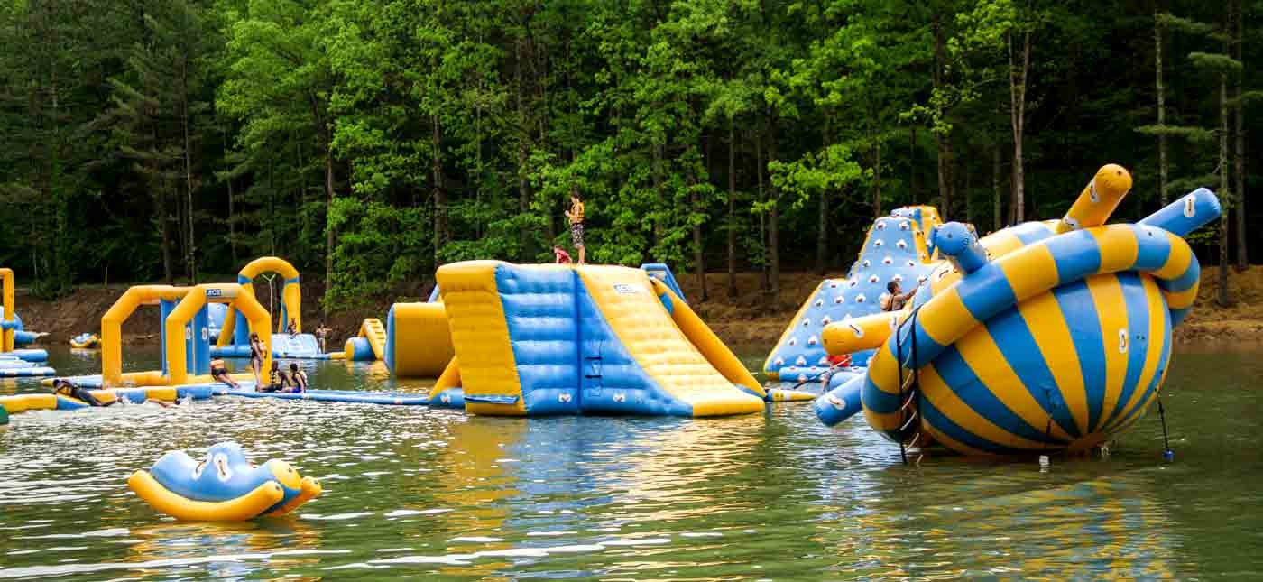 Giant inflatable toys and obstacles to play on float on the lake at Wonderland Waterpark.