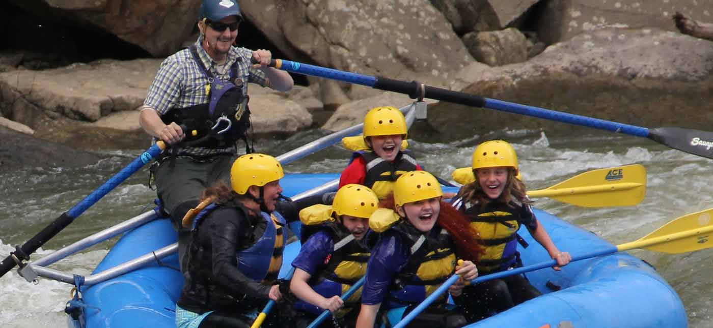 A kids group goes down the New River in an OAR boat with a guide on a whitewater rafting trip in the New River Gorge, West Virginia.