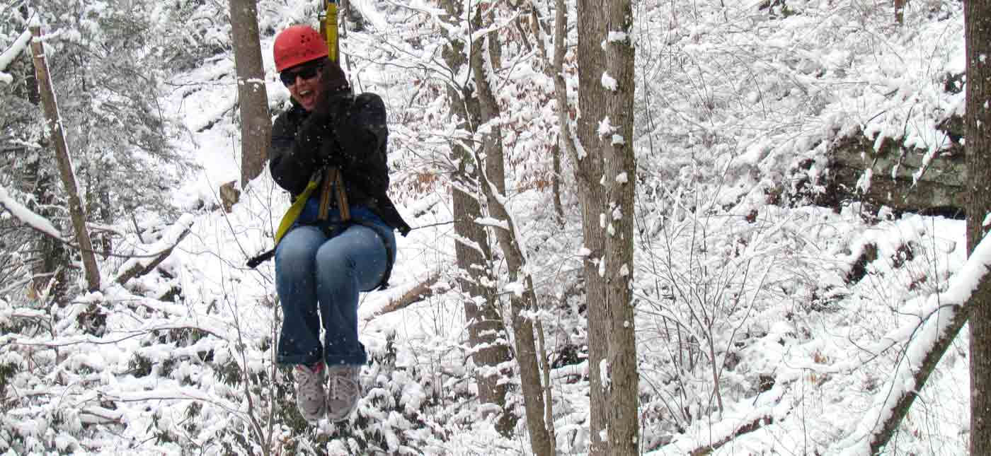A woman rides a zip line along the New River Gorge in winter time.