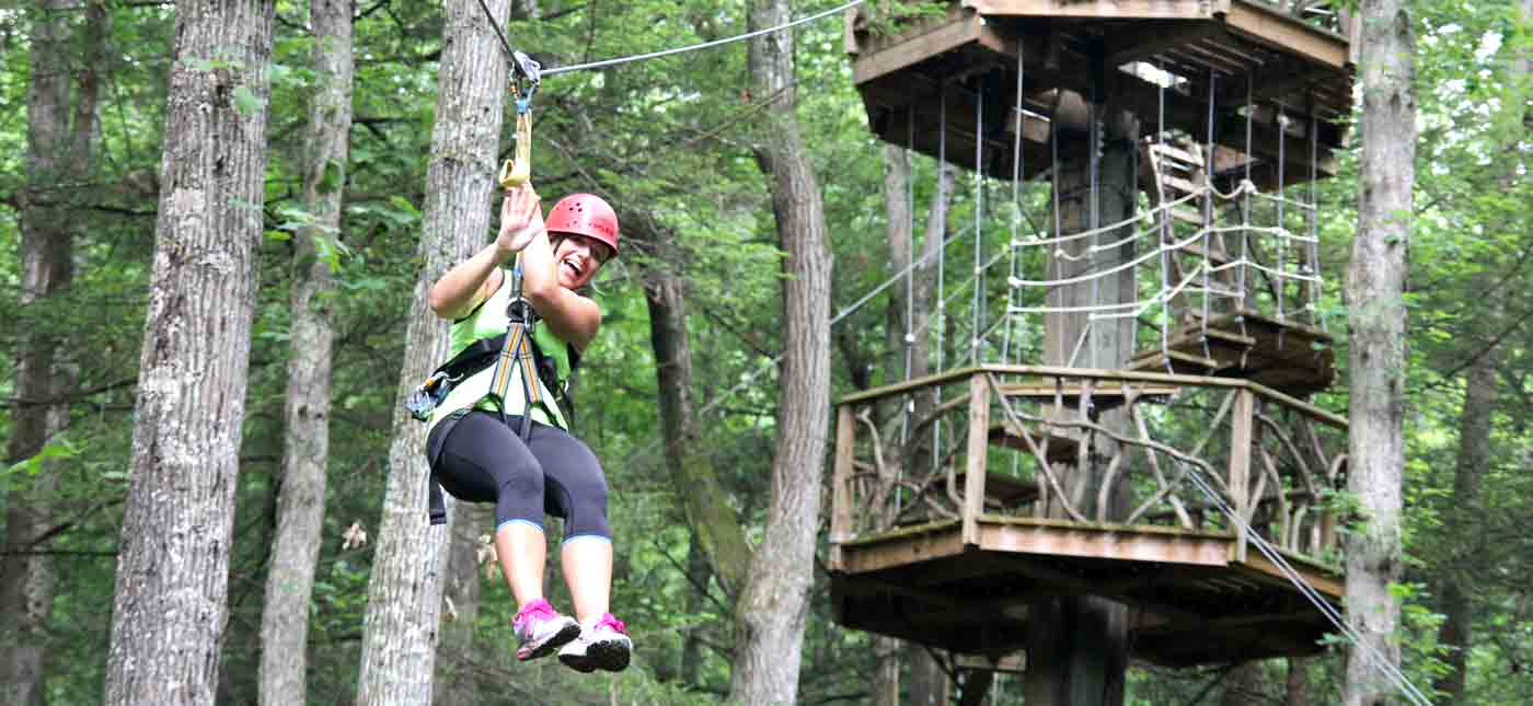 A woman rides the zip line off the tree tower on the canopy zip line tour.