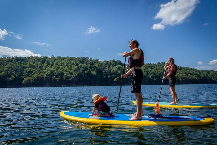a family paddleboards at summersville lake