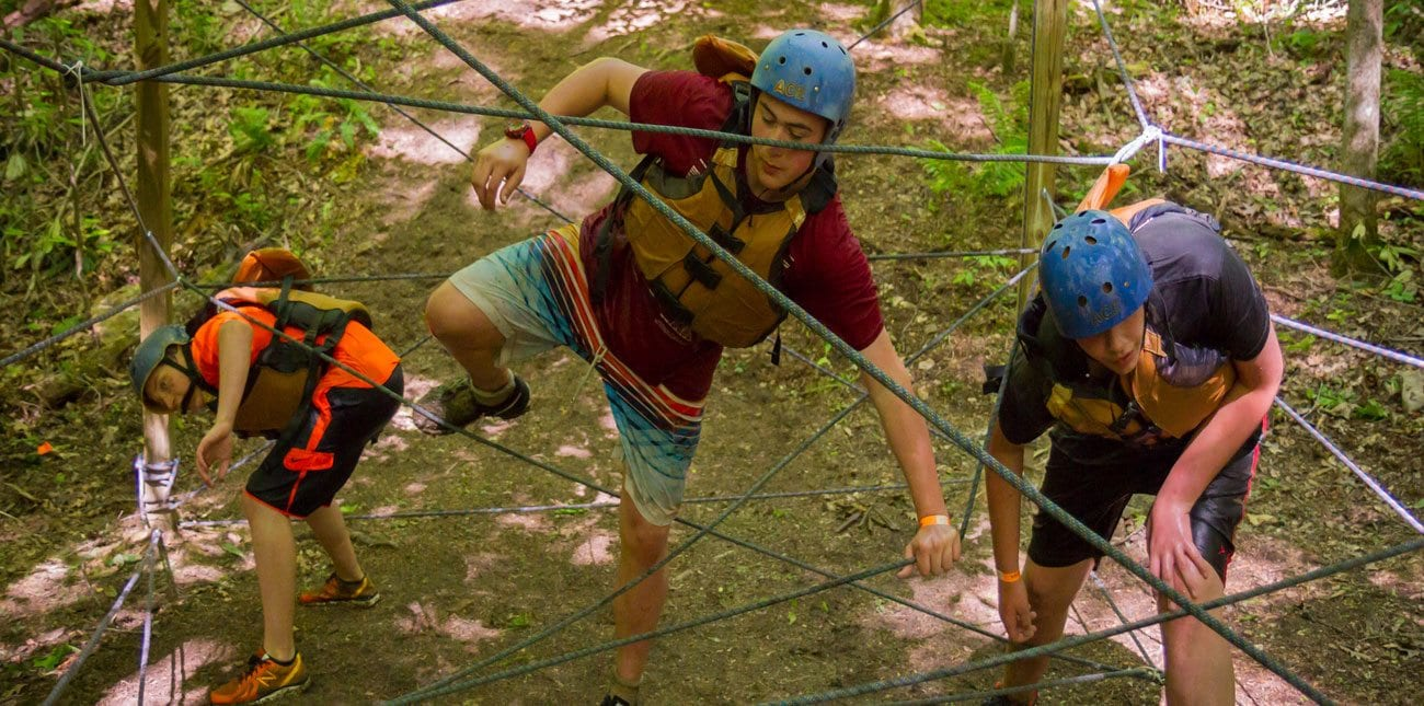 boys climbing through ropes on course