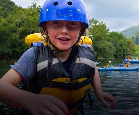 A young boy enjoys a rafting trip on the upper new river with ace adventure resort.