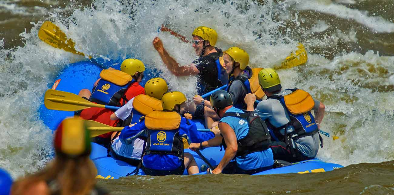 An ACE Adventure Resort raft hits a huge wave on the new river gorge during a spring rafting trip.