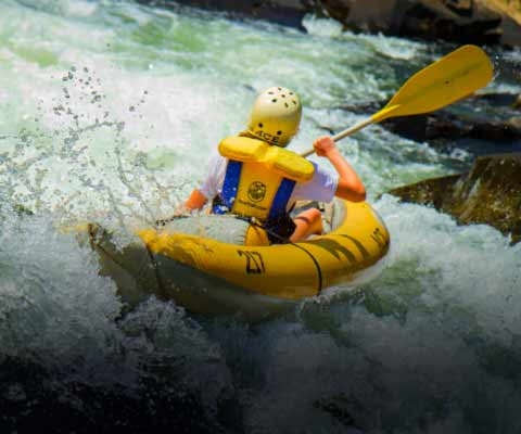 A rafter runs the summer gauley river in an inflatable ducky.