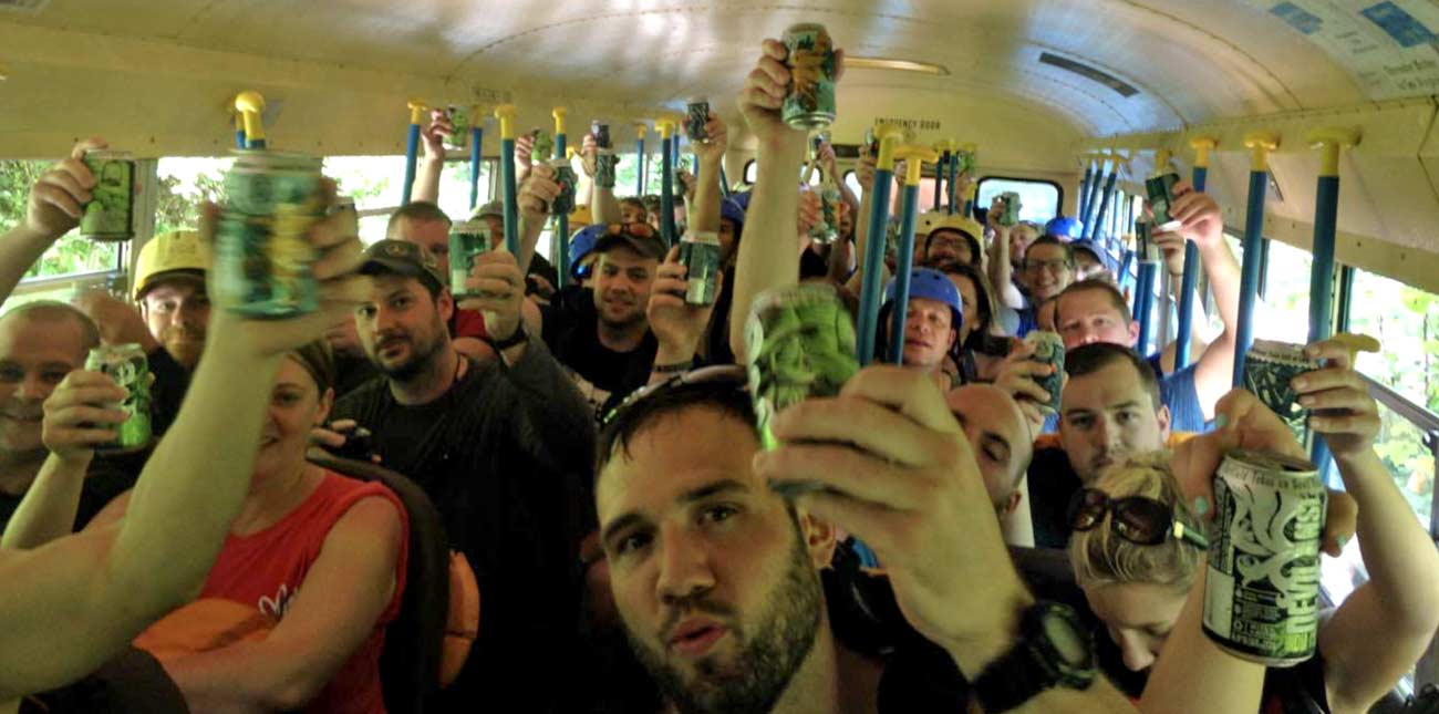 A group of ACE whitewater rafters celebrate their rafting trip by toasting cans of GVBC Devil Anse IPA on the ACE bus.
