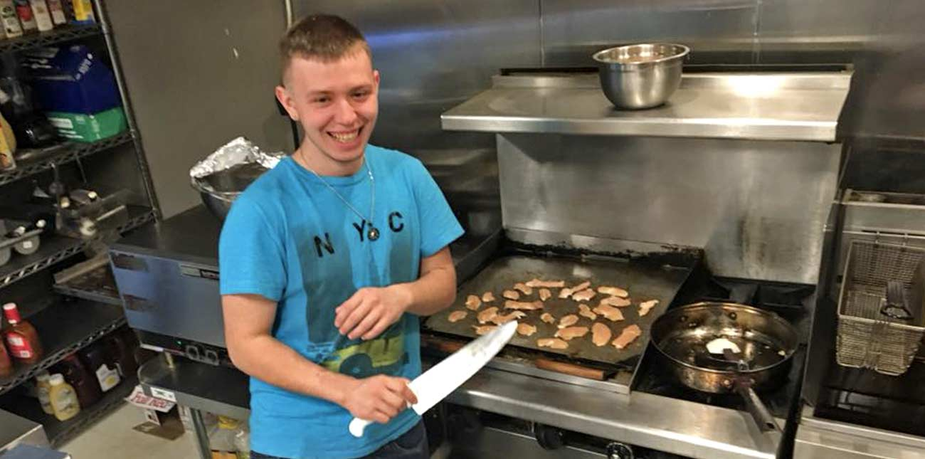 The chef in the kitchen at Pinheads Bowling in Oak Hill, West Virginia, prepares chicken on the grill for dinner.