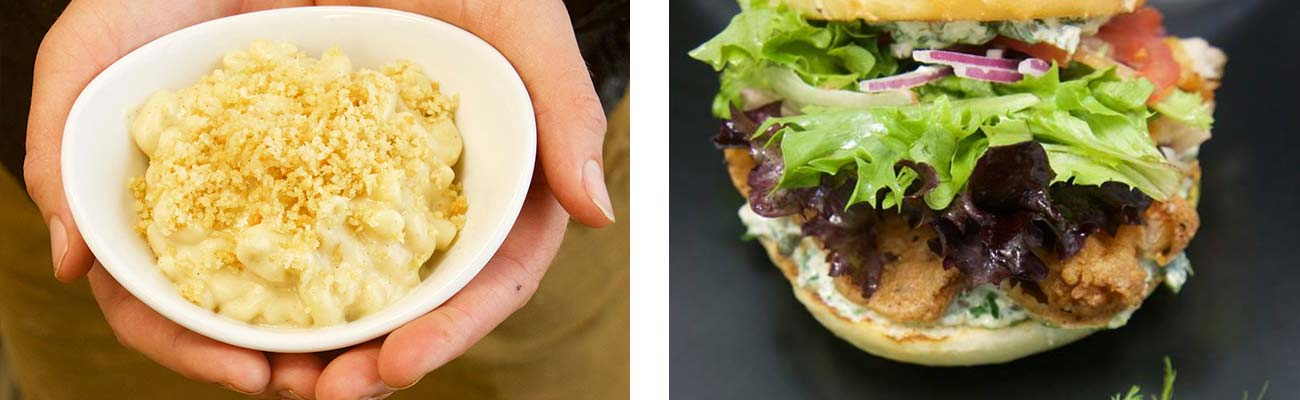 Hands present a serving of macaroni and cheese on the left, and a fried fish sandwich on the right at Secret Sandwich Society in Fayetteville, West Virginia.