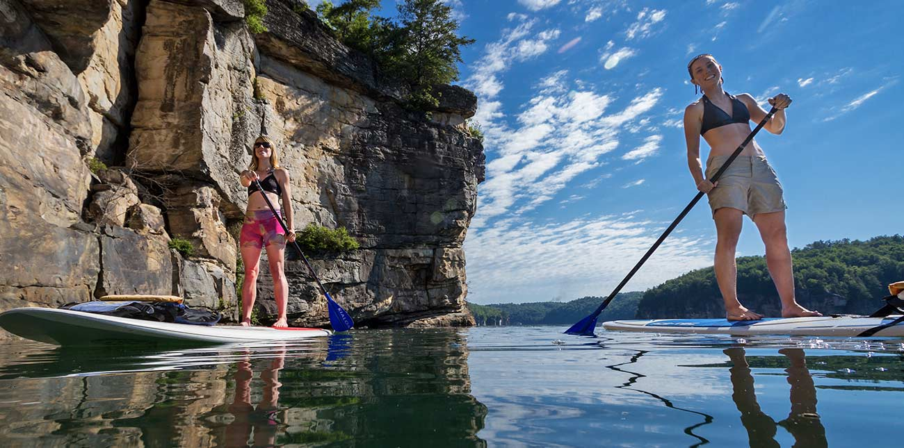 Two friends paddle across the water under a cliff line at Summersville Lake on the pontoon adventure trip.