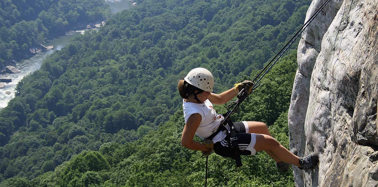 A woman rappels down the rock face of the lower New River Gorge.
