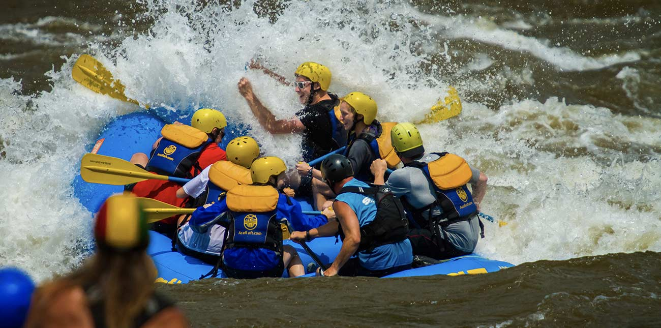 Rafters on the Lower New River plow through a big whitewater wave.