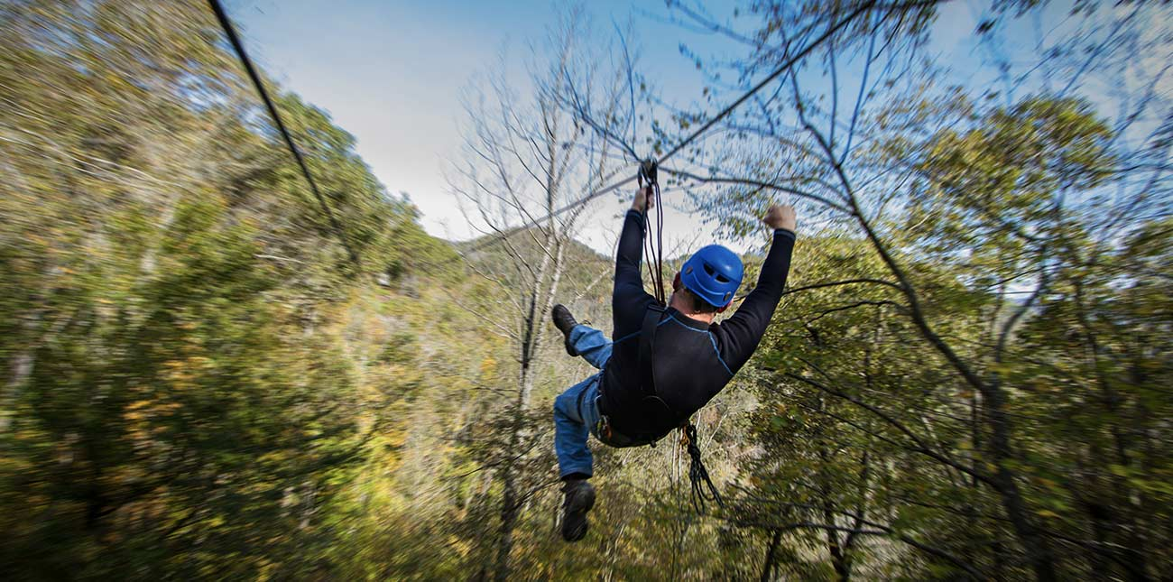 A canopy zip line tour flying through the trees at ACE Adventure Resort in West Virginia.