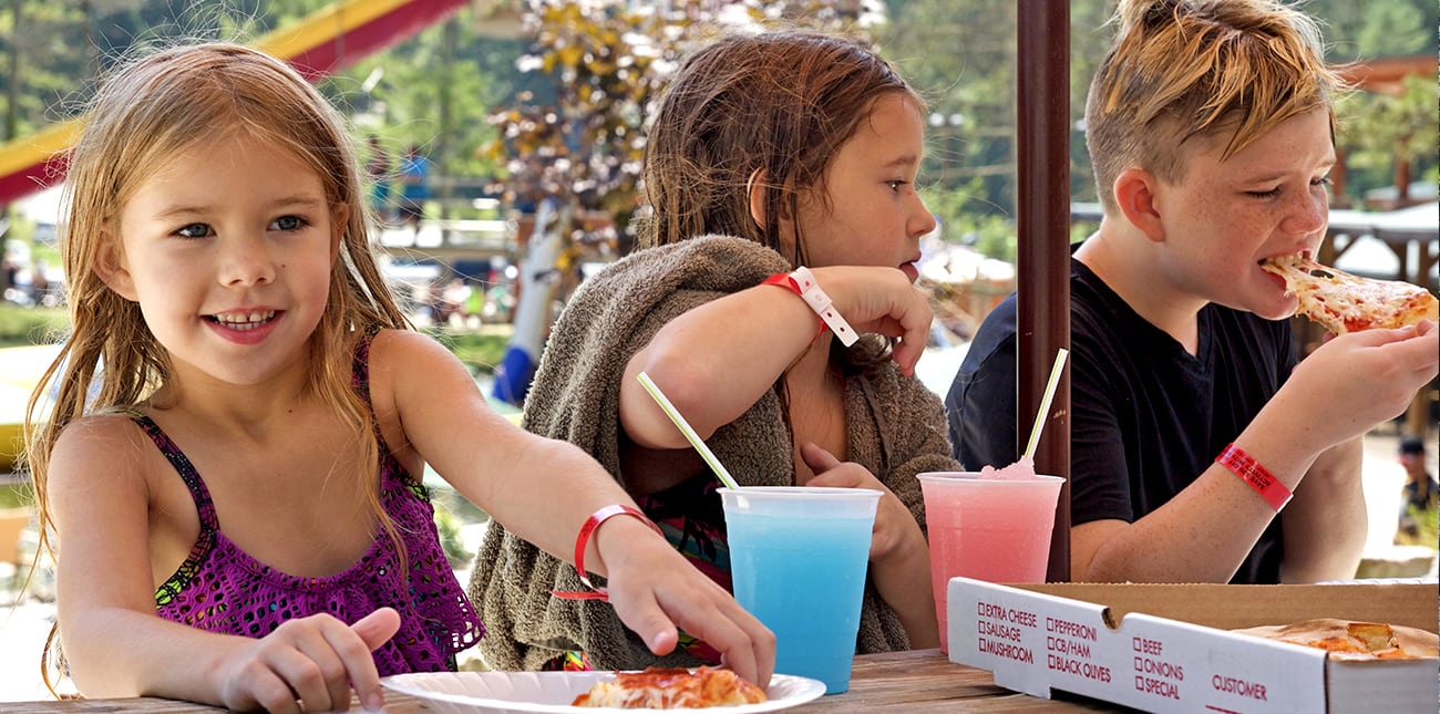 Kids pizza party with fruit slushies on the patio umbrella deck at Wonderland Waterpark at ACE Adventure Resort.