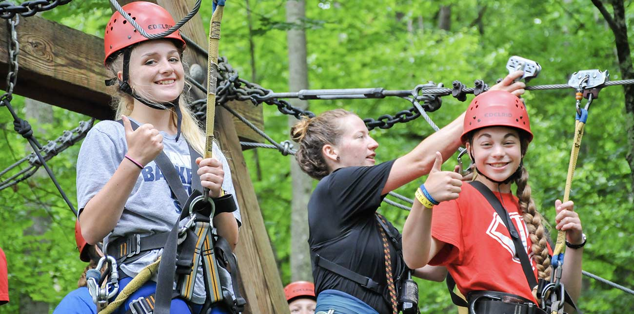 A group of girls on a school trip with ACE get clipped into the ziplines, and prepare to take off on a cliffside zip trip at ACE Adventure Resort.