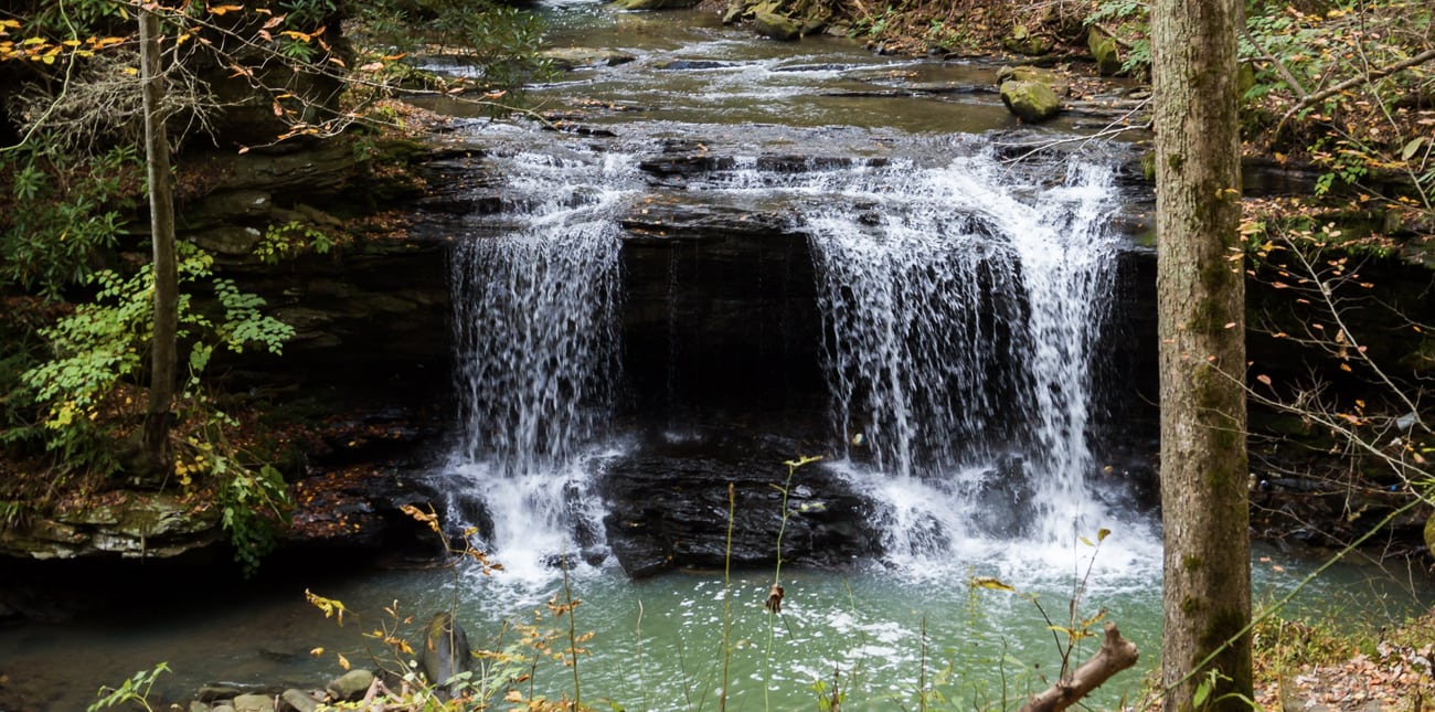 A waterfall along a hiking trail at ACE Adventure Resort pours into the creek.