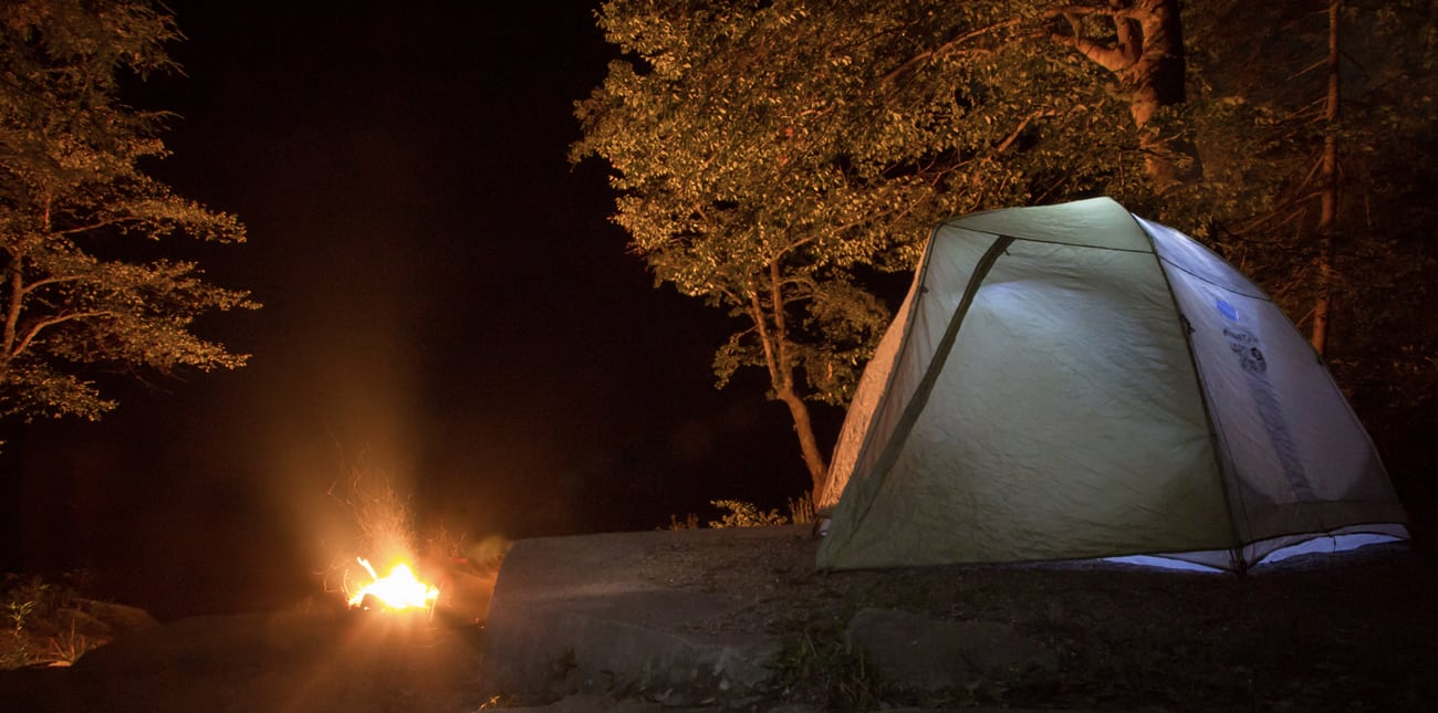 An overnight campsite glows next to the fire under the stars on a camping trip with ACE Adventure Resort in West Virginia.