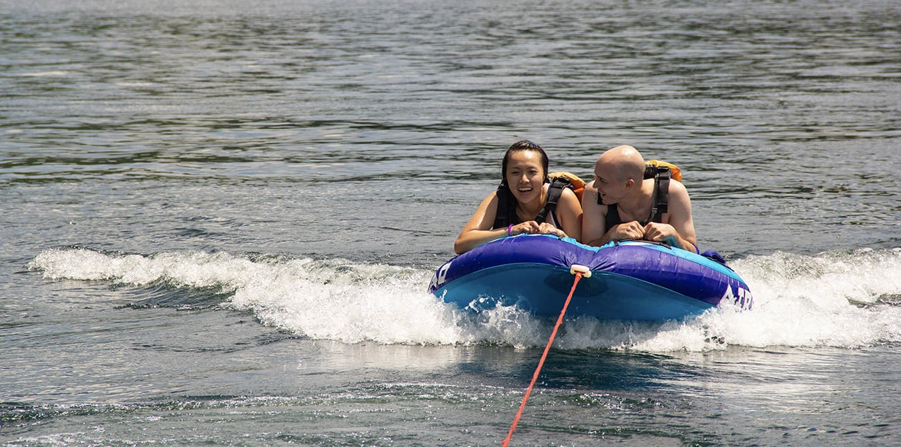Guests of ACE Adventure Resort ride a speeding inflatable towed by a pontoon boat on the Summersville Lake Multi-sport Adventure Trip.