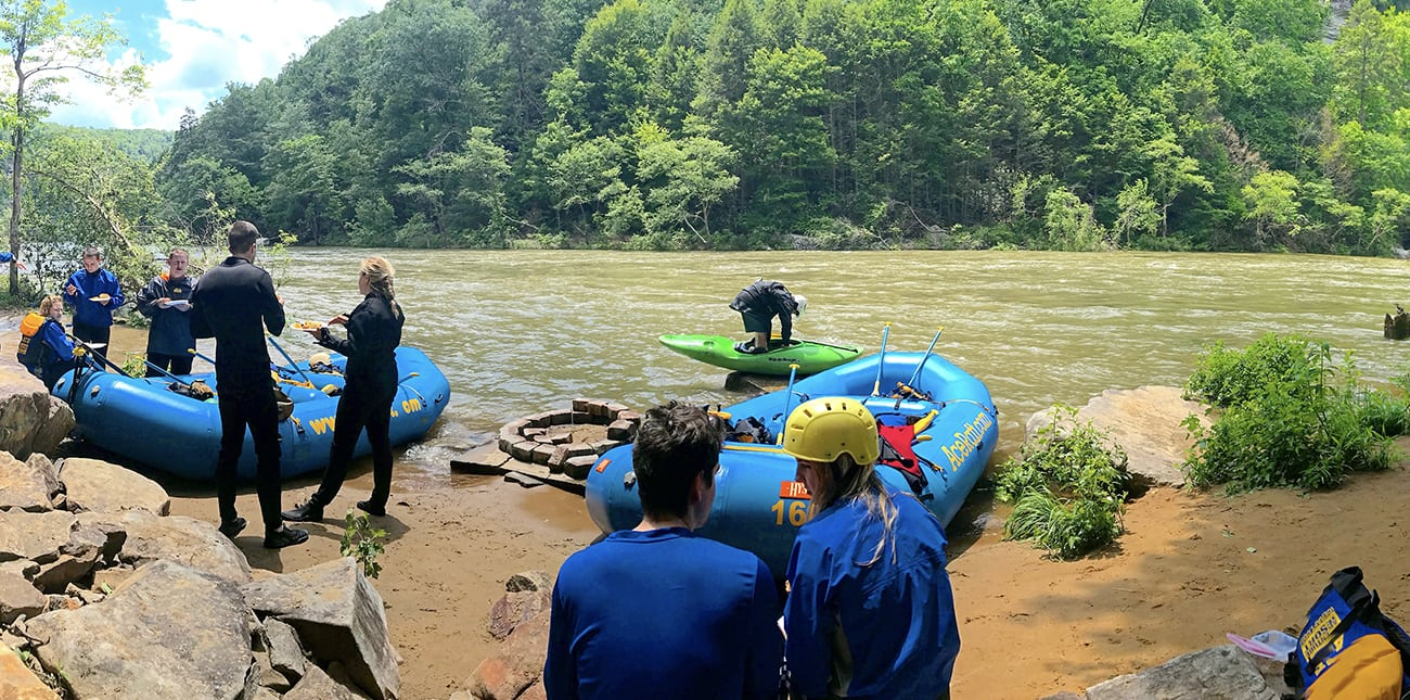 A couple eat lunch next to the river at ACE's private lunch spot next to the lower Gauley river on a rafting trip with ACE Adventure Resort in West Virginia.