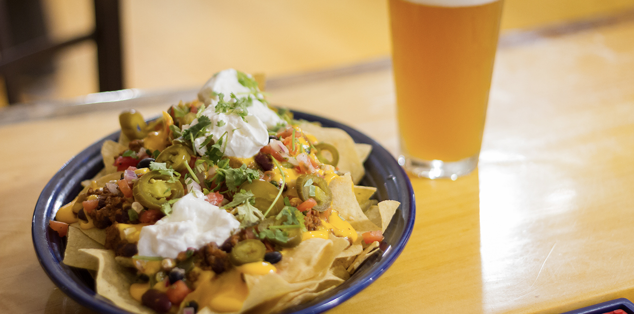 A loaded plate of nachos with the works and craft beer on tap at The Lost Paddle, one of the best Oak Hill restaurants in the New River Gorge.