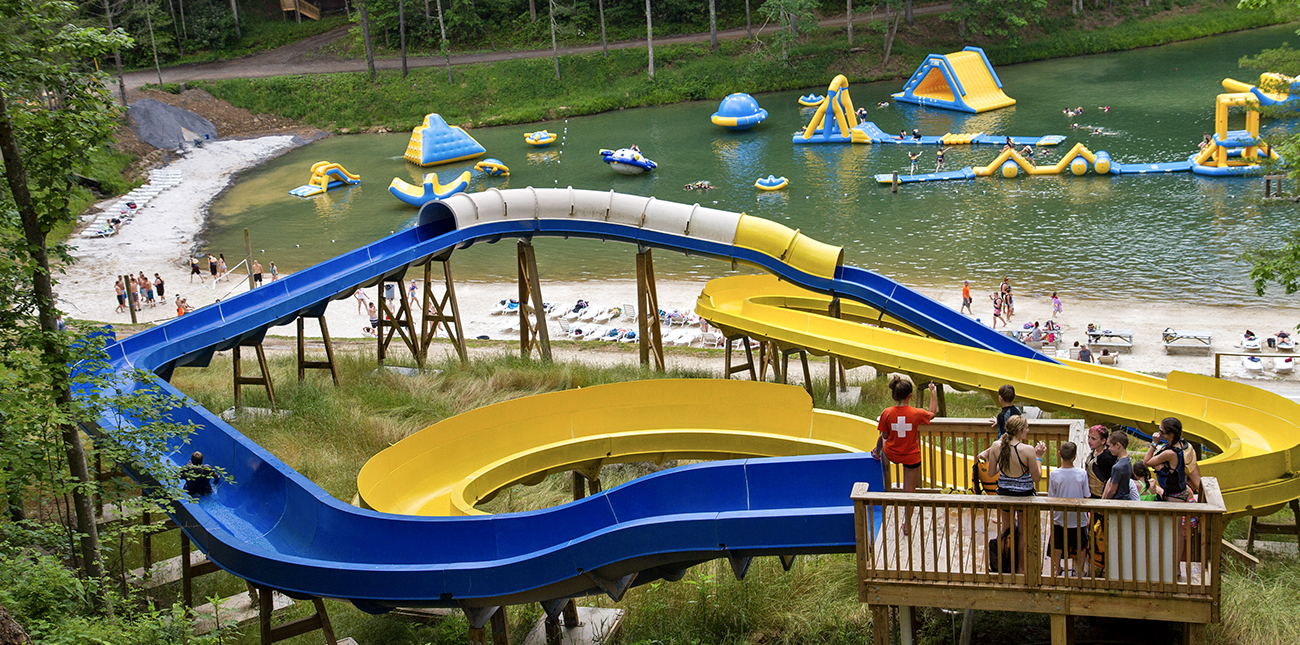 Two waterslides overlook ACE lake and the beach at wonderland waterpark at ACE Adventure Resort, open during the 2019 GIRL Fest in the New River Gorge.