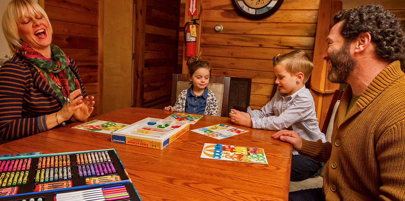 A family plays games inside their winter lodging cabin at ACE Adventure Resort in the New River Gorge.