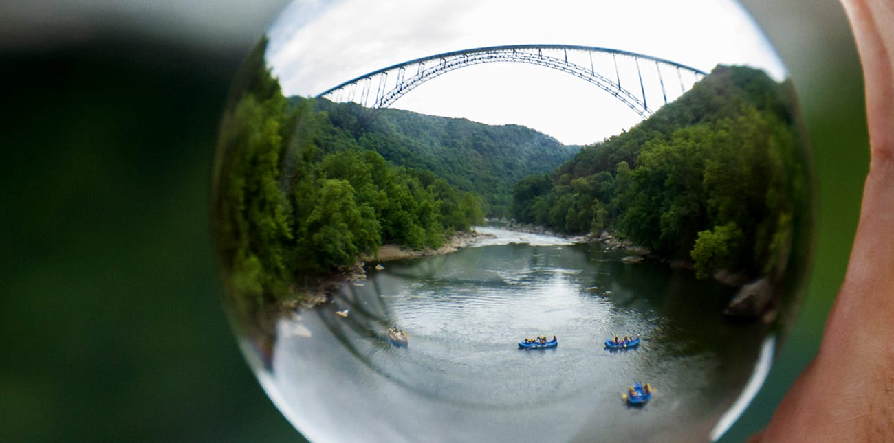 Rafts pass under the New River Gorge Bridge, the best known landmark of west virginia whitewater rafting.