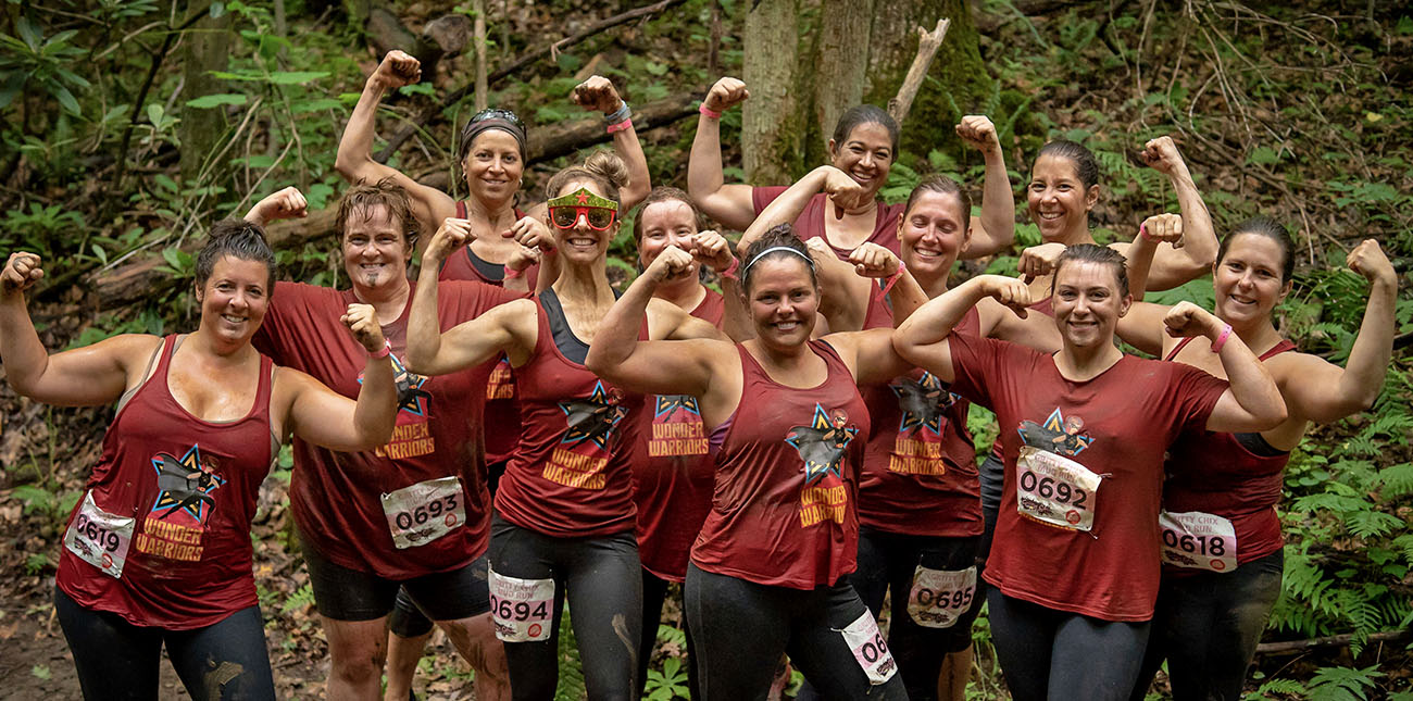 A group of Gritty Chix pose on the mud course during the Gritty Chix Mud Run at ACE Adventure Resort in the New River Gorge, WV.