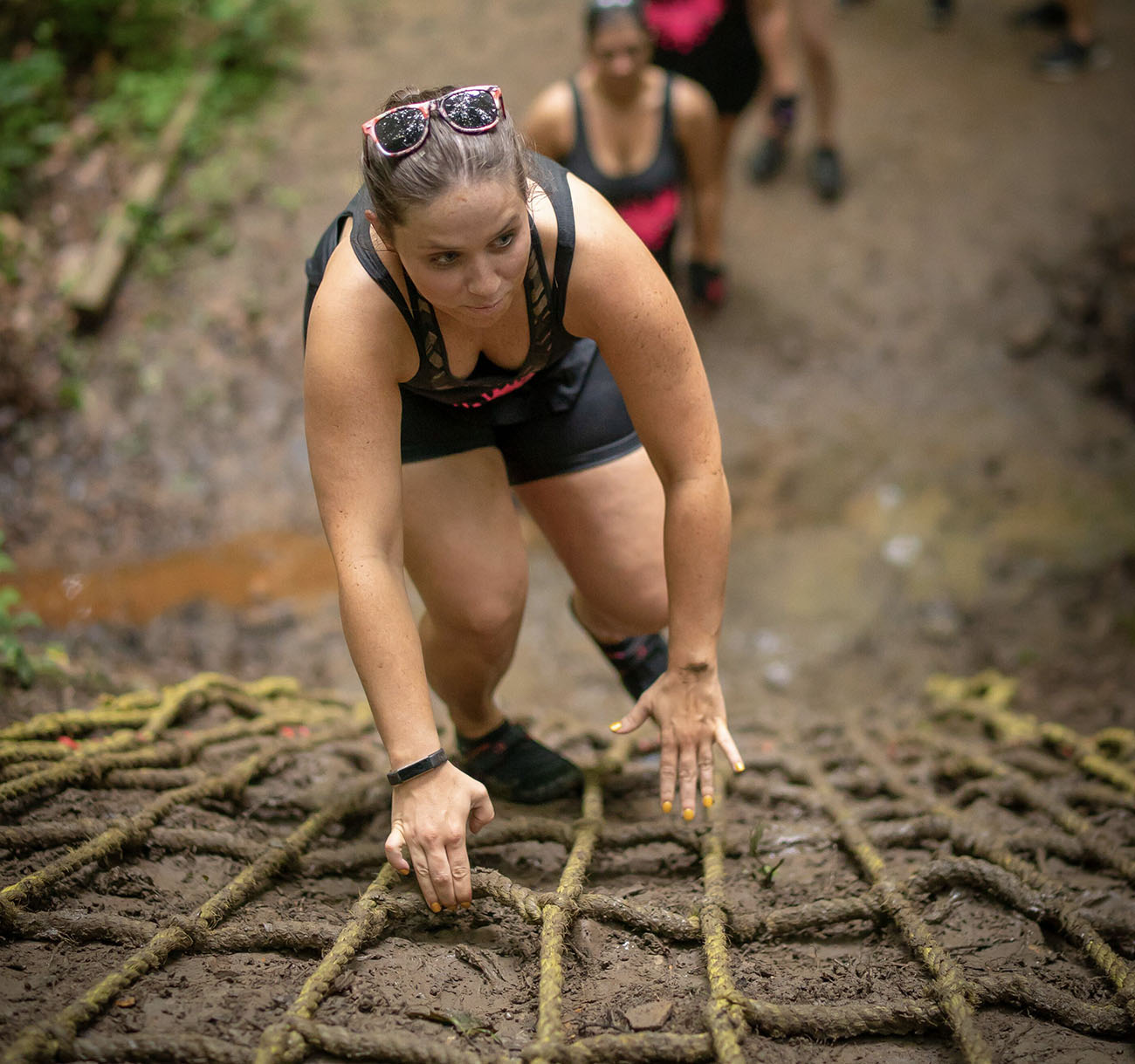 A woman climbs the rope ladder during the 2018 Gritty Chix Mud Run at ACE Adventure Resort in Southern WV.