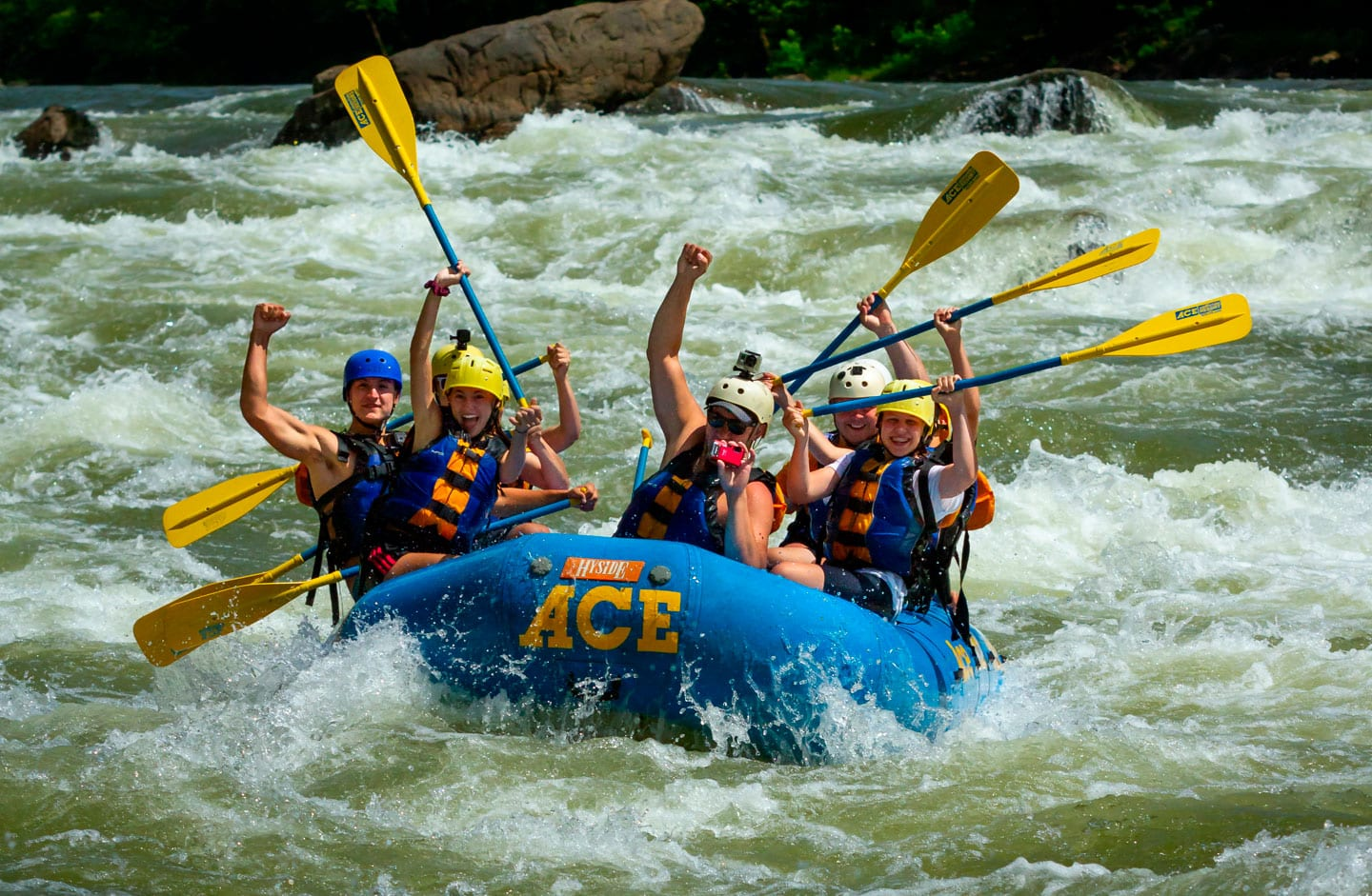 A family smiles and cheers on their lower new river gorge rafting trip while running fayette station rapid.