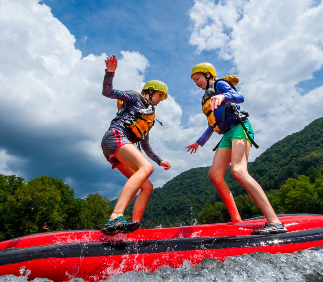Two young girls play on top of an inflatable kayak on an upper new river gorge trips during summer rafting season.