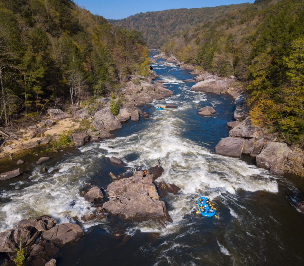 A drone shot aerial view of a raft running the hawaii 5 0 wave in Lost Paddle Rapid during a gauley river rafting trip with ACE Adventure Resort in West Virginia.