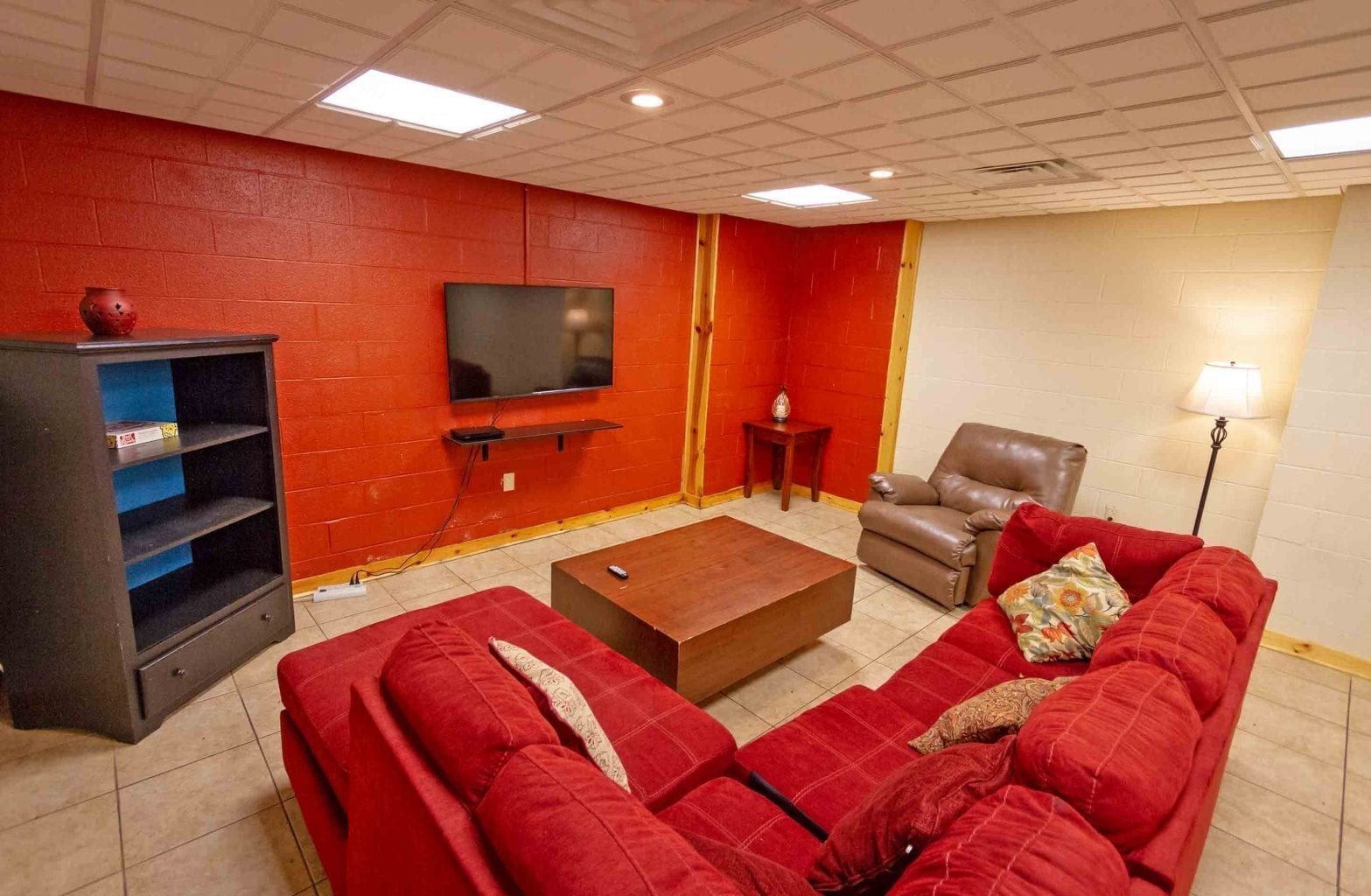 A view of the television and sectional couch in the basement of Red Fox Log Home at ACE Adventure Resort.
