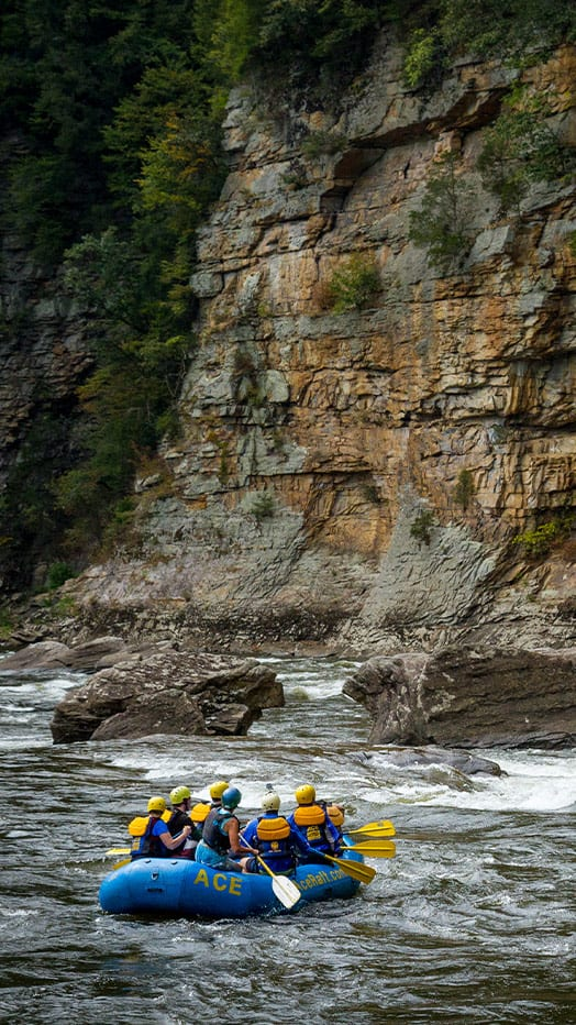 A raft passes a gorgeous cliff line on the lower gauley during fall rafting season in west virginia.