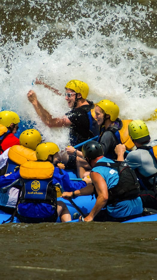 A 16 foot raft hits a giant wave head one during spring rafting season