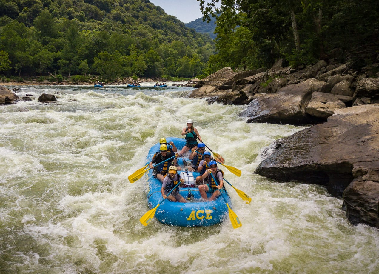 Several boats on a new river gorger rafting trip run the keeney's rapids with a mountain backdrop.