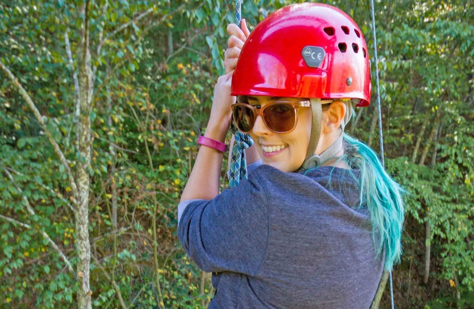 A woman swings from the ropes and smiles on the Team Challenge Course alpine tower at ACE Adventure Resort in the New River Gorge, West Virginia.