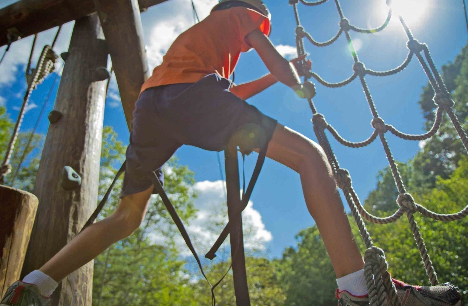 A kid jumps up the rope on the Team Challenge Course at ACE Adventure Resort