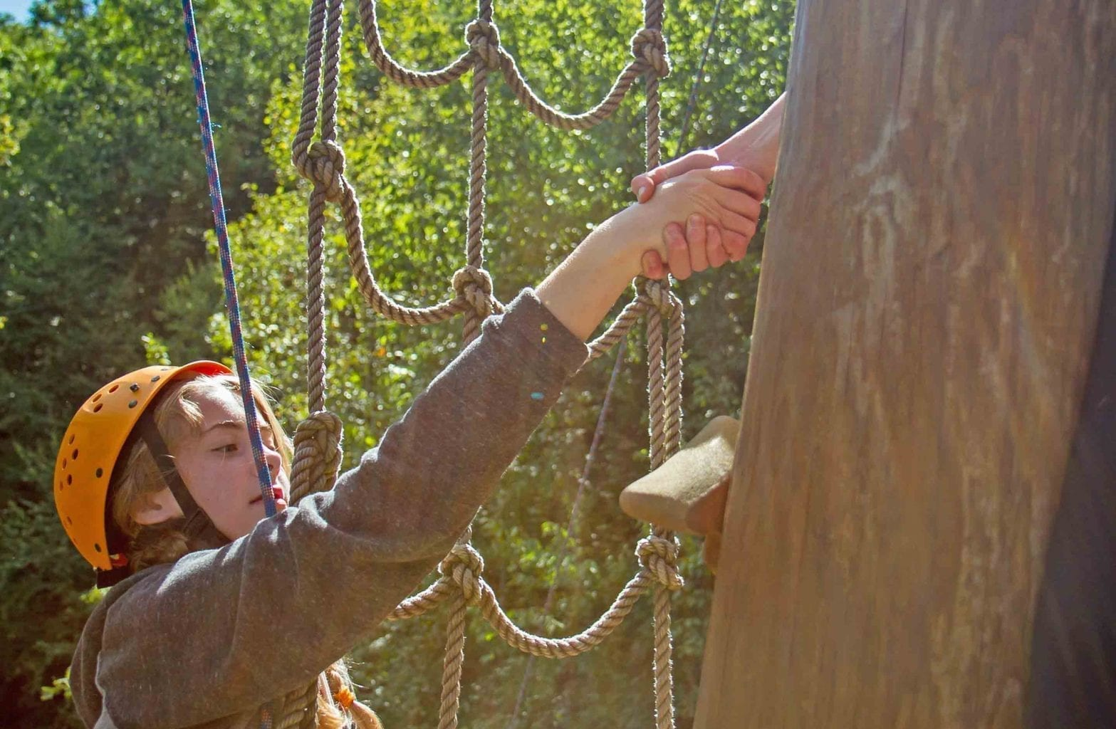A kid climbs the ropes on the alpine tower on the Team Challenge Course at ACE Adventure Resort.