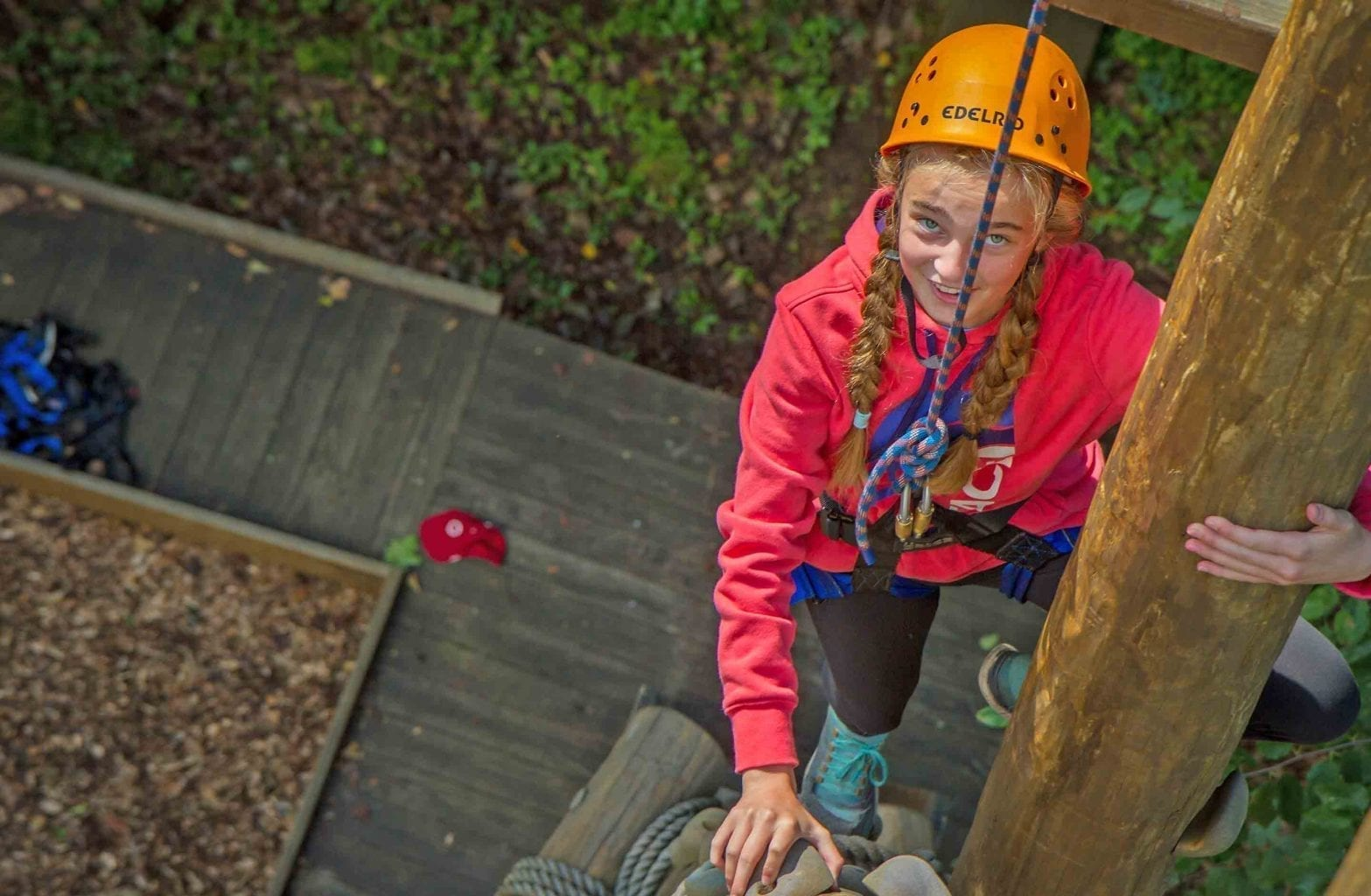 A girl climbs the ropes on the Team Challenge Course at ACE Adventure Resort.