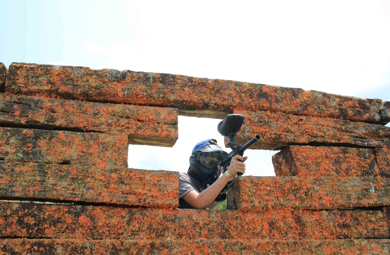 A teenager playing paintball peers over his gun through a combat barrier on the walkon paintball course at ACE Adventure Resort.
