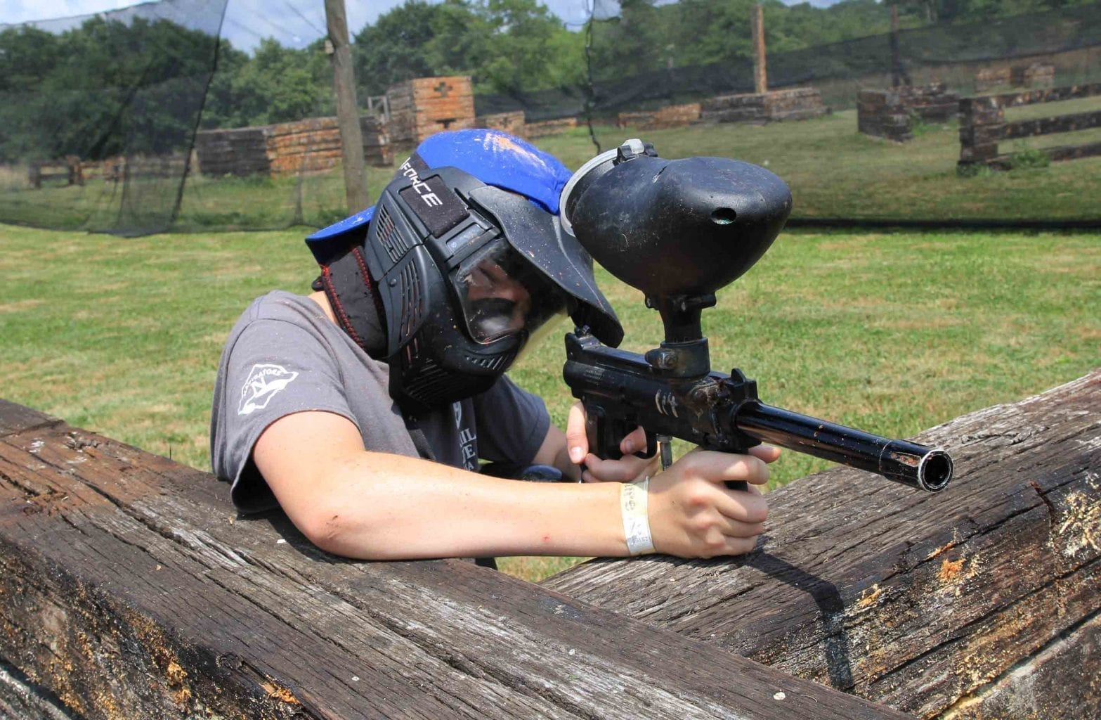 An older kid plays paintball on the walk on paintball course at ACE.