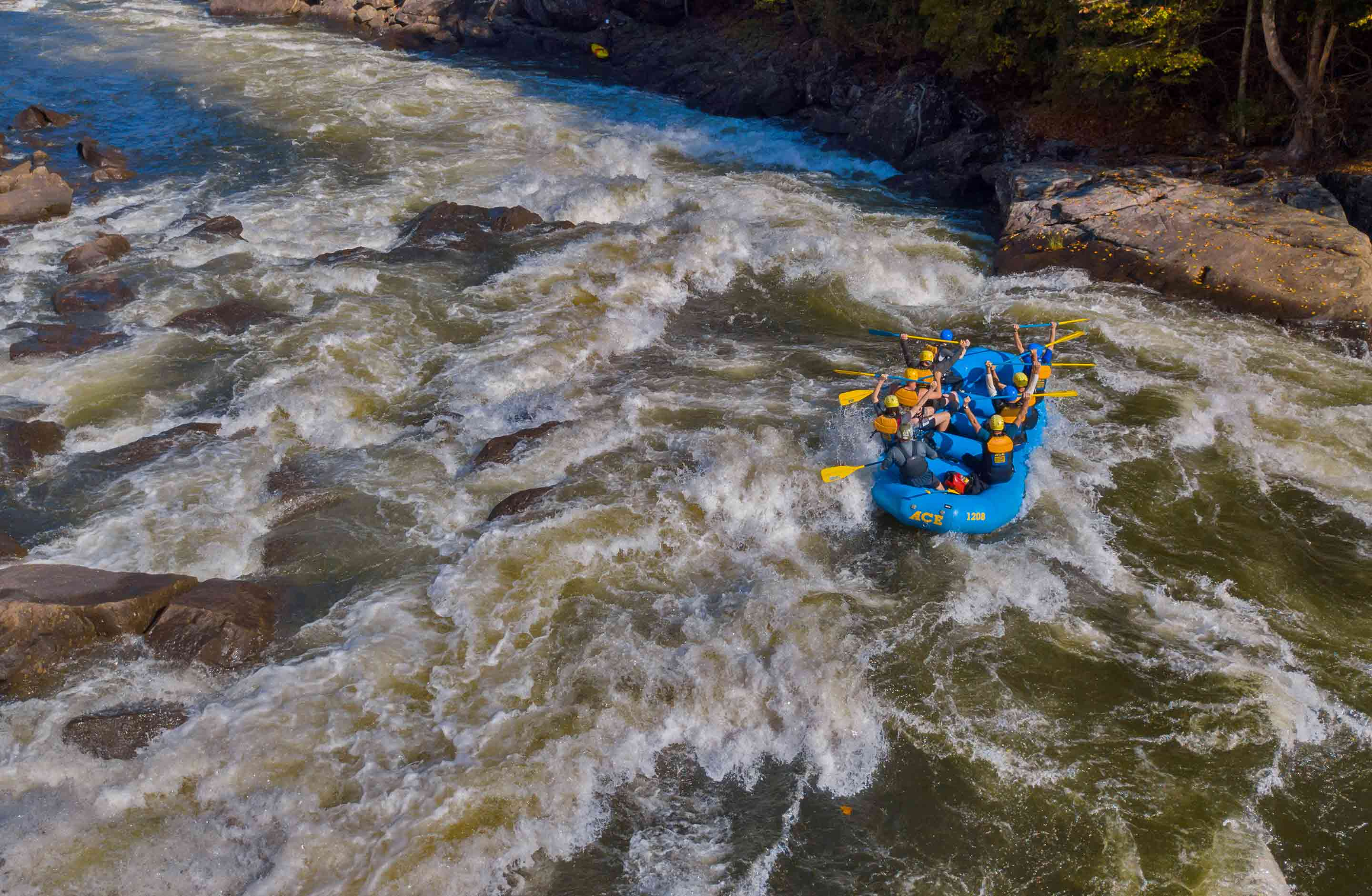 A 6 person raft appears tiny in the massive waves of the Upper Gauley on a Gauley River rafting trip with ACE Adventure Resort.