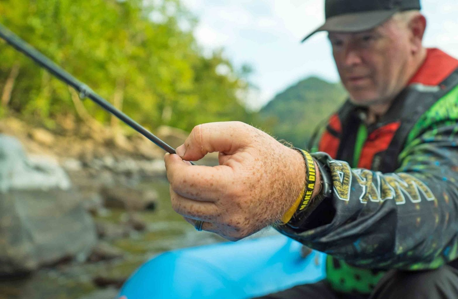 A fisherman casts his rod into the Lower New River on a guided fishing trip with ACE Adventure Resort