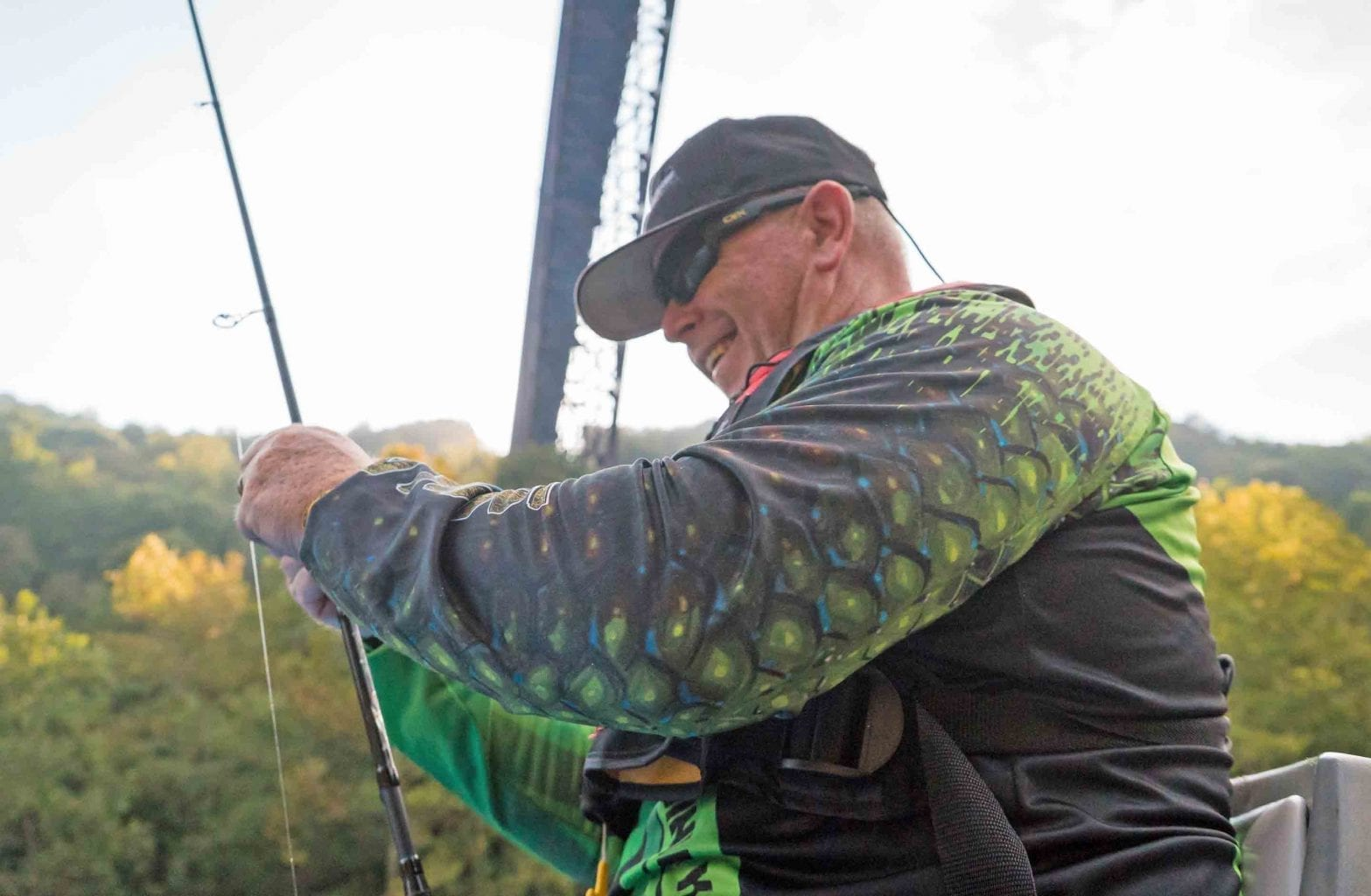 A man ties the lure onto his fishing rod on a guided float fishing tour under the New River Gorge Bridge with ACE Adventure Resort